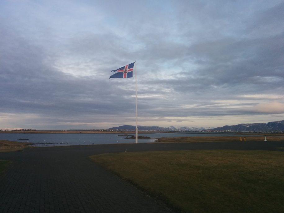 Islandijos vėliava kalnų ir ežero fone